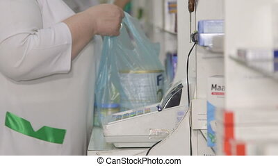 pharmacy checkout counter - Pharmacist assistant selling...
