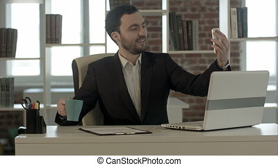 Businessman using smartphone to take picture of himself