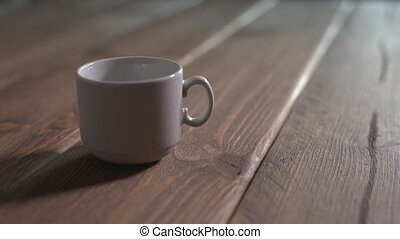 pours hot coffee into a cup placed on the wooden desk