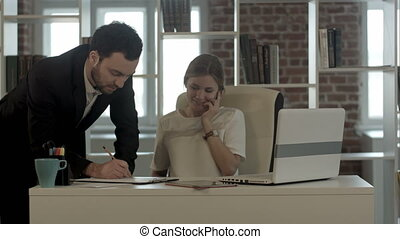 Portrait of a woman making a phone call while her colleague is working in a office