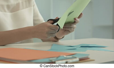 Woman is cutting green paper using scissors