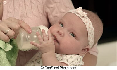 Young mother is feeding her baby milk