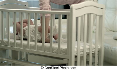Mother caressing her cute baby girl sleeping in a cot