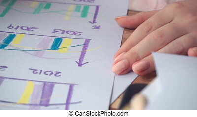 Woman drawing different business math graphs: diagrams,...