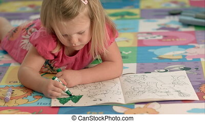 Cute little girl is drawing with felt-tip pen