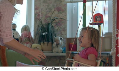 Smiling mother and child on swing