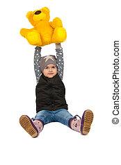 cheerful girl holding a teddy bear on her head.