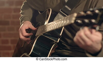 Man playing guitar on a stage. Musical concert. Close-up...