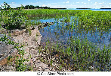 Lake landscape - Lake edge with red granite rocks and...