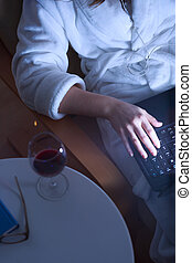 Drinking wine and surfing the net - Young woman drinking...