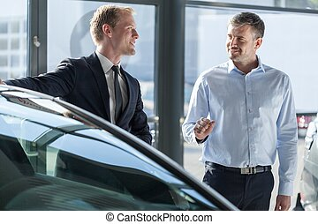 Car dealer showing vehicle - Photo of car dealer showing...