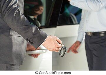 Car dealer giving car keys - Close up of car dealer giving...