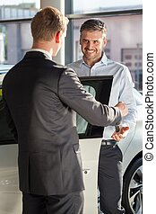 Salesman in car dealership - Image of salesman in car...
