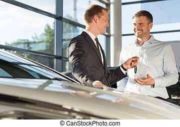 Car dealer selling car - Photo of car dealer selling car to...