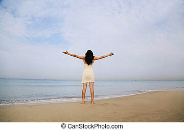 beautiful woman standing on the shore of the beach