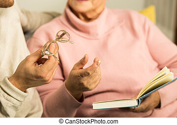 Giving senior woman reading glasses - Male carer giving...