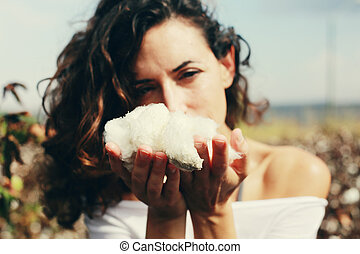 beautiful woman holding natural cotton. Focus on the arms