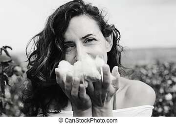 beautiful woman holding natural cotton. Focus on the face