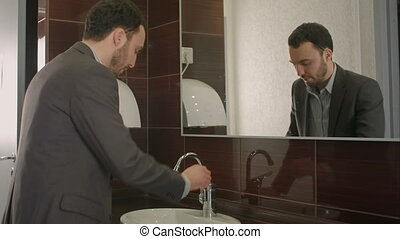 Businessman washing face in bathroom. People