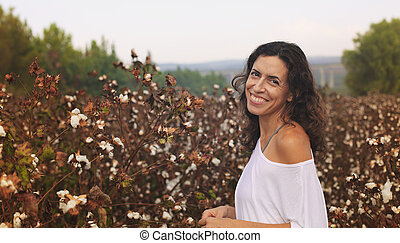 Portrait of beautiful 35 years old woman standing in cotton...