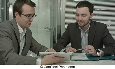 Image of two young businessmen using touchpad at meeting....