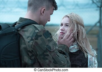 Young soldier farewell - Couple is looking at each other and...