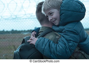 Father coming home - Son is hugging his dad returning from...