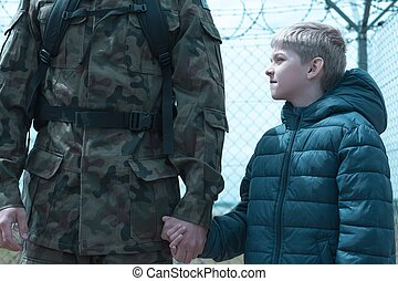Son and dad - Little boy is holding his father soldier hand