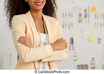 Beauty female fashion designer standing with crossed arms