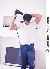 handsome man using  hairdryer