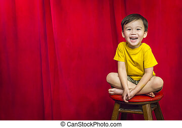 Laughing Boy Sitting on Stool in Front of Curtain - Laughing...