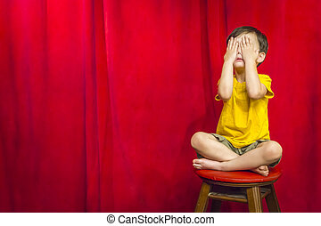 Boy Covering Eyes Sitting on Stool in Front of Curtain -...