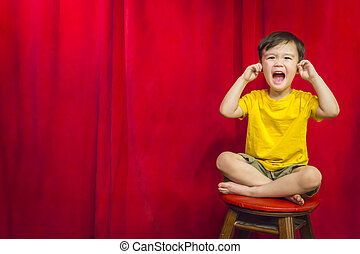 Boy, Fingers In Ears on Stool in Front of Curtain - Mixed...