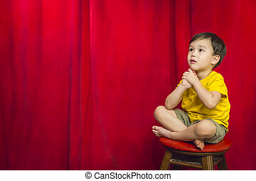 Mixed Race Boy Sitting on Stool in Front of Curtain -...