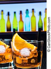 detail of two glasses of spritz aperitif aperol cocktail with orange slices and ice cubes on bar table, disco atmosphere background