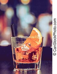glass of spritz aperitif aperol cocktail with orange slices and ice cubes on bar table, vintage atmosphere background