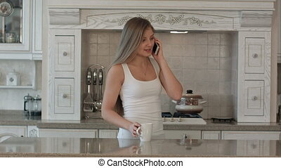Young beautiful woman talking cell phone, drink coffee or tea in the kitchen, happy smile