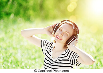Sounds of nature - Young pretty woman enjoying music in...
