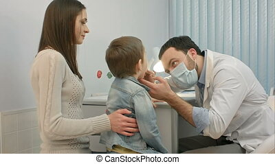 Pediatrician checking little boy throat