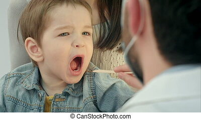 Little boy having throat examination People