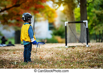 Little kid playing lacrosse with his stick in the autumn...