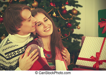 happy tender loving couple in embrace warmed at Christmas tree