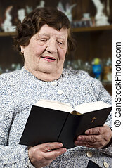 Elderly woman reading bible at home