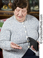 Pensioner counts her last money - Elderly pensioner sitting...