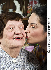 Granddaughter kissing her grandmother - Granddaughter...