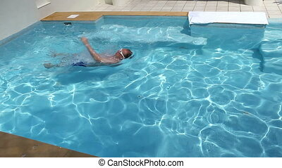 The man swims in pool on back, vignetting - The man swims in...