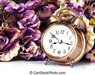 alarm clock with rose vintage flower background soft focus