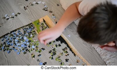 teenager boy collects puzzles  lying on  floor