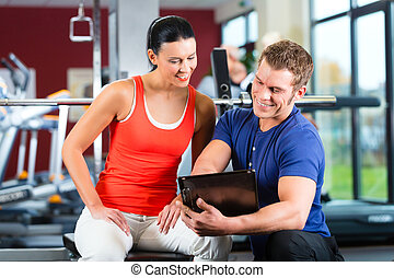 woman and Personal Trainer in fitness gym