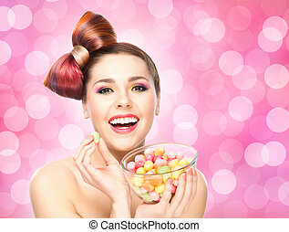 Beautiful smiling girl eating sweets from a bowl on blink...